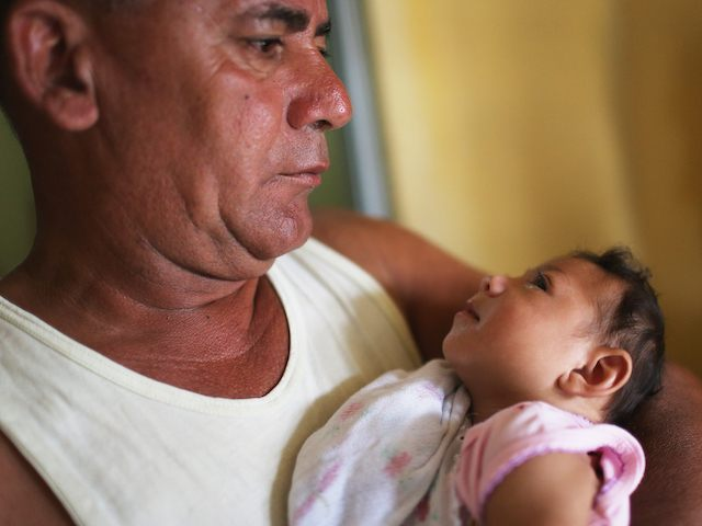 RECIFE, BRAZIL - JANUARY 27: Alice Vitoria Gomes Bezerra, 3-months-old, who has microcephaly, is held by her father Joao Batista Bezerra on January 27, 2016 in Recife, Brazil. In the last four months, authorities have recorded close to 4,000 cases in Brazil in which the mosquito-borne Zika virus may have led to microcephaly in infants. The ailment results in an abnormally small head in newborns and is associated with various disorders including decreased brain development. According to the World Health Organization (WHO), the Zika virus outbreak is likely to spread throughout nearly all the Americas. At least twelve cases in the United States have now been confirmed by the CDC. (Photo by Mario Tama/Getty Images)