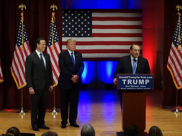 Donald Trump (C) looks on with Rick Santorm (L) as Mike Huckabee speaks during a Trump campaign rally raising funds for US military veterans at Drake University in Des Moines, Iowa on January 28, 2016. US Republicans scrambling to win the first contest in the presidential nomination race were gearing …