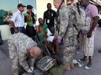 A US Army doctor treats an injured Haitian man at the Port au Prince international airport in Port au Prince on January 15, 2010. The US troops were the first of an estimated 1,000 due to pour into the country over the course of the day. The United States is …