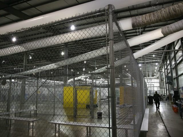 A U.S. Border Patrol agent walks through a detention facility run by the Border Patrol on September 8, 2014 in McAllen, Texas. The Border Patrol opened the holding center to temporarily house the children after tens of thousands of families and unaccompanied minors from Central America crossed the border illegally …