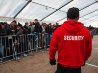 A member of the LAGeso security team watches over asylum-seekers queuing at the State Office of Health and Social Affairs (LAGeSo) registration centre in Berlin on December 10, 2015.