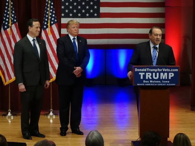onald Trump (C) looks on with Rick Santorm (L) as Mike Huckabee speaks during a Trump campaign rally raising funds for US military veterans at Drake University in Des Moines, Iowa on January 28, 2016. US Republicans scrambling to win the first contest in the presidential nomination race were gearing …