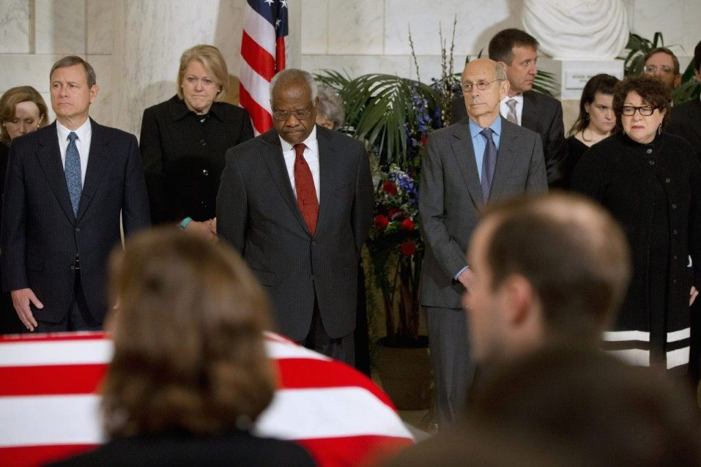 Chief Justice John Roberts, Jr., left, and from second from left, Ginny Thomas, next to her husband, Justice Clarence Thomas, Justice Stephen Breyer, and Justice Sonia Sotomayor, attend a private ceremony in the Great Hall of the Supreme Court in Washington, Friday, Feb. 19, 2016, where late Supreme Court Justice Antonin Scalia lies in repose. (AP Photo/Jacquelyn Martin, Pool)