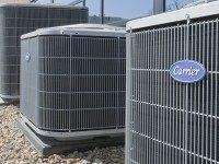 Air conditioners of the Carrier brand, a United Technologies company, are installed in Omaha, Neb., Tuesday, April 21, 2009. United Technologies Corp. said Tuesday its first-quarter profit fell 28 percent as the industrial conglomerate coped with falling orders related to the drop in office and residential construction. Declines were led …