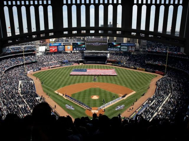 A large American flag is unfurled on the field at Yankee Stadium, Monday, April 6, 2015 in New York.
