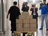 A staff member delivers President Barack Obama's fiscal 2017 federal budget to the House Budget Committee Room on Capitol Hill in Washington, Tuesday, Feb. 9, 2016. President Barack Obama unveils his eighth and final budget, a $4 trillion-plus proposal that's freighted with liberal policy initiatives and new and familiar tax …