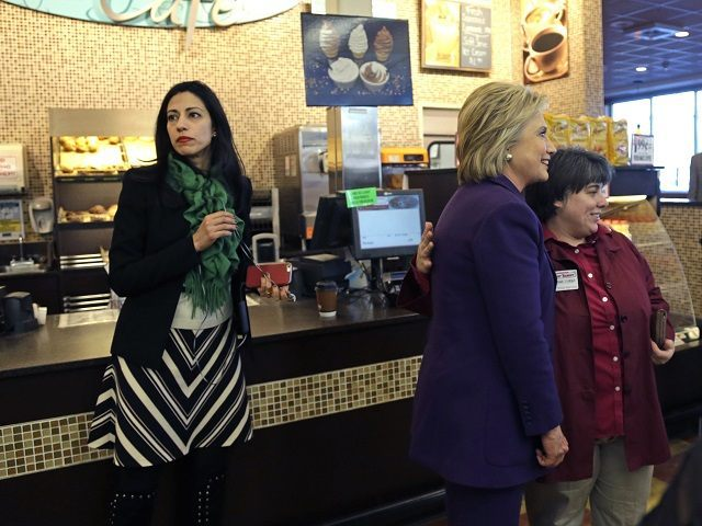 Huma Abedin, left, aide to Democratic presidential candidate Hillary Clinton, right, waits as she poses for a photo with an employee at Market Basket Supermarket, Tuesday, Feb. 2, 2016, in Manchester, N.H. (AP Photo/Elise Amendola)