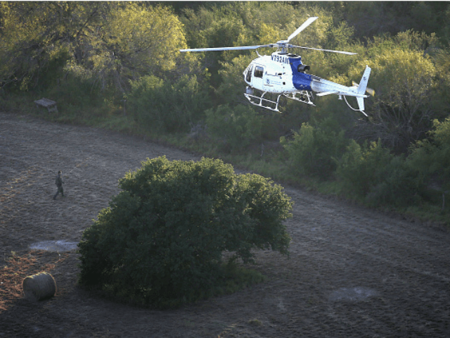 A helicopter from U.S. Air and Marine Operations (AMO), searches for undocumented immigrants near the U.S.-Mexico border on December 9, 2015 at near Mission, Texas. The number of migrant families and unaccompanied minors from Central America crossing into the U.S. has again surged in recent months. (Photo by