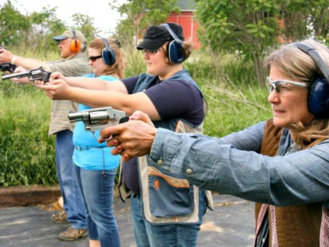 Darlene DeMaagd of Barry County, right, and her daughters, Amy, and Krista, and husband, Ross, left, shoot at targets on their range behind their rural Barry County home. Photo taken June 12, 2011. ( Rex Larsen | The Grand Rapids Press ) SLUG: CONCEALED GUNS PERMITS MICHIGAN