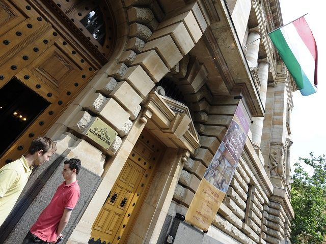 Local citizens walk in front of the headquarters of the Hungarian National Bank (MNB) in downtown Budapest on June 7, 2010. Hungary's new government pledged to keep its finances under control today after comments by senior officials the country was broke rocked the markets, the euro and investor confidence. AFP …