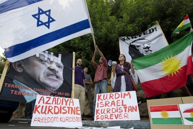 Israelis of Kurdish origin hold up Kurdish and Israeli flags as well portraits of Turkey's Prime Minister Recep Tayyip Erdogan, whom they labelled a 'terrorist', during a demonstration outside the Turkish embassy in Tel Aviv on July 8, 2010