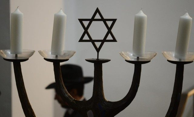 A man walks past a menorah during a ceremony to ordain four rabbis at the synagogue in Cologne, western Germany, on September 13, 2012