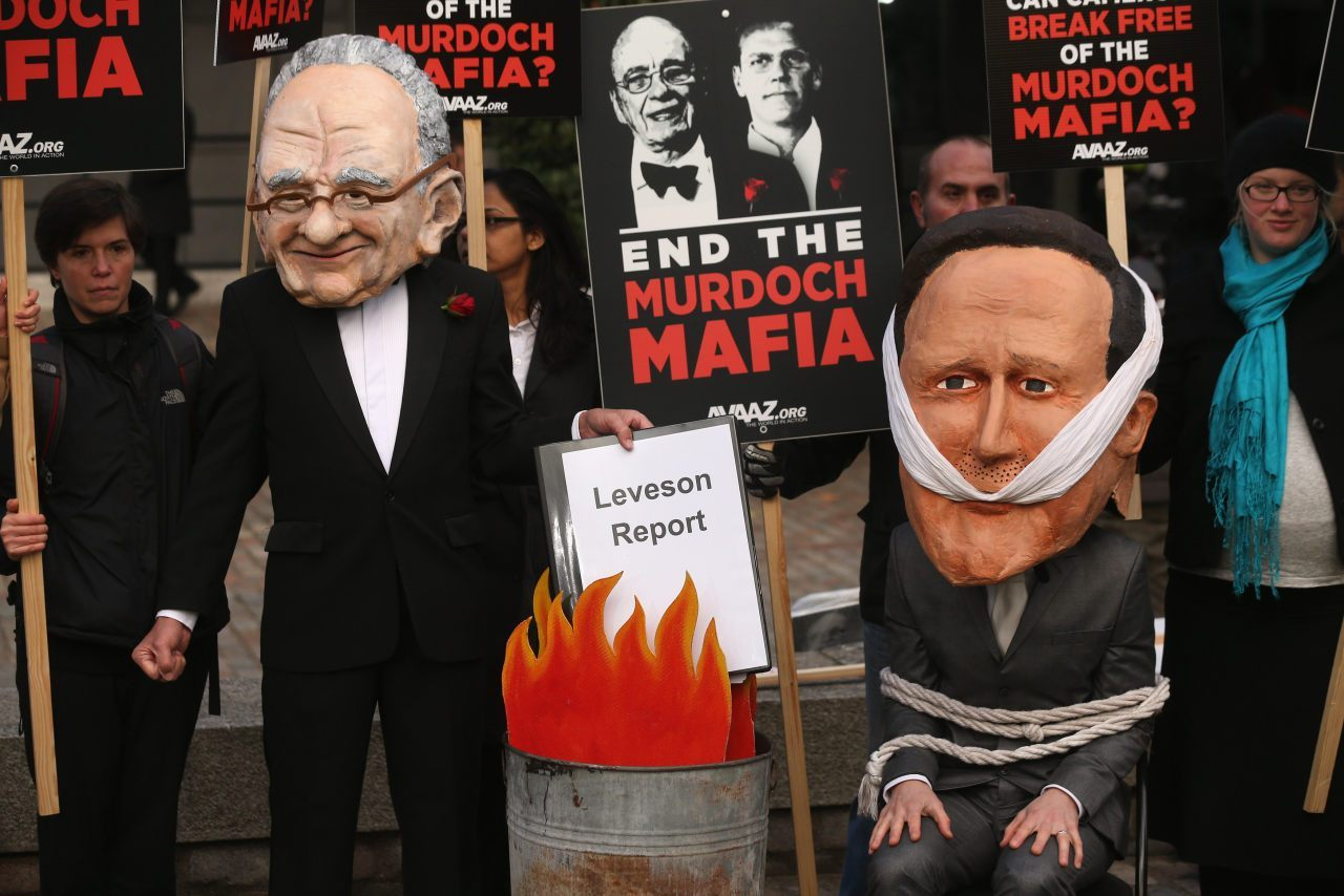 LONDON, ENGLAND - NOVEMBER 29: A protest group campaigning against the political dominance of Rupert Murdoch stage a mock burning of a copy of the Leveson Report outside the Queen Elizabeth II centre on November 29, 2012 in London, England. The findings of the Leveson Inquiry, which focused on the culture, practices and ethics of the press, was published today after a 16 month inquiry. (Photo by Oli Scarff/Getty Images)