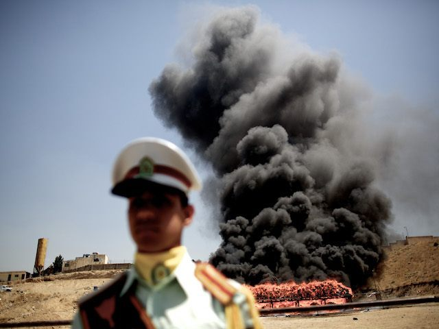 An Iranian employee of the anti-drug police watches 50 tons of drugs seized in recent months burning in eastern Tehran on June 26, 2013 to mark the International Day Against Drug Abuse and Illicit Trafficking. AFP PHOTO/BEHROUZ MEHRI (Photo credit should read BEHROUZ MEHRI/AFP/Getty Images)