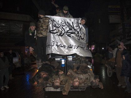 Opposition fighters, wave the flag of Ahrar al-Sham brigade, as they parade in the northern Syrian city of Aleppo on February 19, 2015 the bodies of alleged government troops they said were killed in recent clashes in the Aleppo region. The Syrian regime is ready to suspend aerial bombardment of …