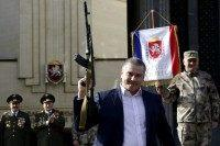 Russian acting leader of Crimea Sergei Aksyonov (C) holds a model of AK-47 automatic rifle during the celebration of Defender of the Fatherland Day in the Crimean city of Simferopol on February 23, 2015