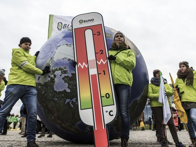 BERLIN, GERMANY - NOVEMBER 29:  A woman stays in front of a model of the earth holding a thermometer as activists participate in the Global Climate March on November 29, 2015 in Berlin, Germany. The COP21 2015 Paris Climate Conference will begin on November 30, though due to the recent Paris terror attacks French police have banned activists from marching in Paris. Large-scale marches are instead taking place in other cities, including today in Berlin.  (Photo by Carsten Koall/Getty Images)