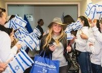 Jewish new immigrant from France, Alexandra Schneider, who is making Aliyah (Immigration to Israel) is welcomed by Israelis waving national flags upon her arrival at Ben Gurion International airport on December 8, 2015 in Lod, about 15 kms east of Tel Aviv, during the Jewish holiday of Hanukkah.