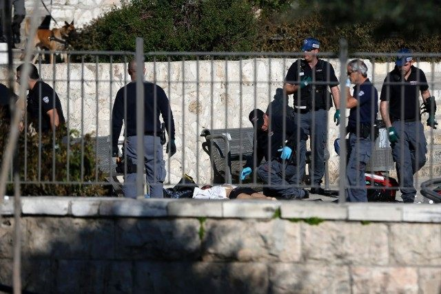 Israeli police officers investigate on the body of one of the reported Palestinian assailants killed during an attack at Damascus Gate, a main entrance to Jerusalem's Old City on February 3, 2016.
