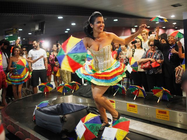 RECIFE, BRAZIL - FEBRUARY 04: Carnival dancers perform for people arriving in the baggage claim area at Guararapes Gilberto Freyre International Airport on February 4, 2016 in Recife, Pernambuco state, Brazil. Officials say as many as 100,000 people may have already been exposed to the Zika virus in Recife, although most never develop symptoms. Tourists are arriving in the city for its famed Carnival celebrations which begin tomorrow. (Photo by Mario Tama/Getty Images)