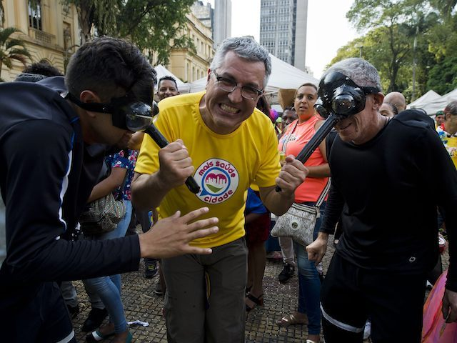 Sao Paulo's Health Secretary, Alexandre Padilha (C), holds two revellers dressed as mosquitos by their proboscis masks, during a street carnival in the Brazilian city of Sao Paulo, on February 4, 2016. . The World Health Organization on Thursday advised countries against accepting blood donations from people who have travelled to regions affected by the Zika virus, as Spain announced Europe's first known case of the disease in a pregnant woman. The mosquito-borne virus has so far spread to 26 countries in South and Central America and the Caribbean and health authorities have warned it could infect up to four million people on the continent and spread worldwide. Since October, Brazil has reported 404 confirmed cases of microcephaly -- up from 147 in 2014 -- plus 3,670 suspected cases. AFP PHOTO / NELSON ALMEIDA / AFP / NELSON ALMEIDA (Photo credit should read NELSON ALMEIDA/AFP/Getty Images)
