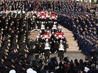Honour guards carry the Turkish flag-draped coffins of car bombing victims during a funeral ceremony at Kocatepe Mosque in Ankara on February 19, 2016. Turkey has detained three more suspects over the attack on a convoy of military buses in Ankara that killed 28 people, prosecutors said on February 19, …