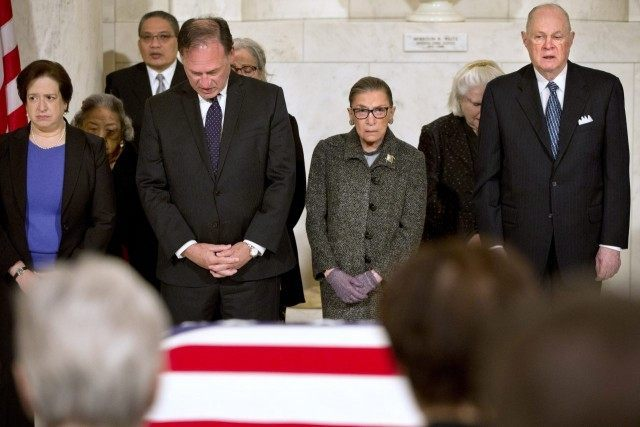 Supreme Court Justices Elena Kagan, left, Samuel Anthony Alito, Jr., Ruth Bader Ginsburg, and Anthony M. Kennedy react during prayers at a private ceremony in the Great Hall of the Supreme Court where late Supreme Court Justice Antonin Scalia lies in repose on February 19, 2016 in Washington, DC. (Photo …