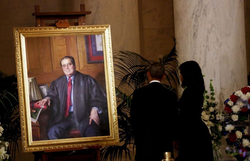 President Obama and First Lady Michelle Obama look at a portrait of Anthony Scalia after paying their respects to Justice Scalia, in front of the casket bearing his body, in the Great Hall of the Supreme Court. (Photo by Aude Guerrucci/Getty Images)