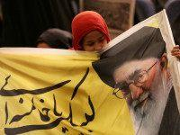 An Iranian girl holds a banner bearing a portrait of supreme leader Ayatollah Ali Khamenei during a campaign meeting of the head of the conservatives' grand coalition of principalists for the upcoming parliamentary elections, Gholam Ali Haddad Adel on February 21, 2016 at Baqiyatallah mosque in the capital Tehran. Voters …