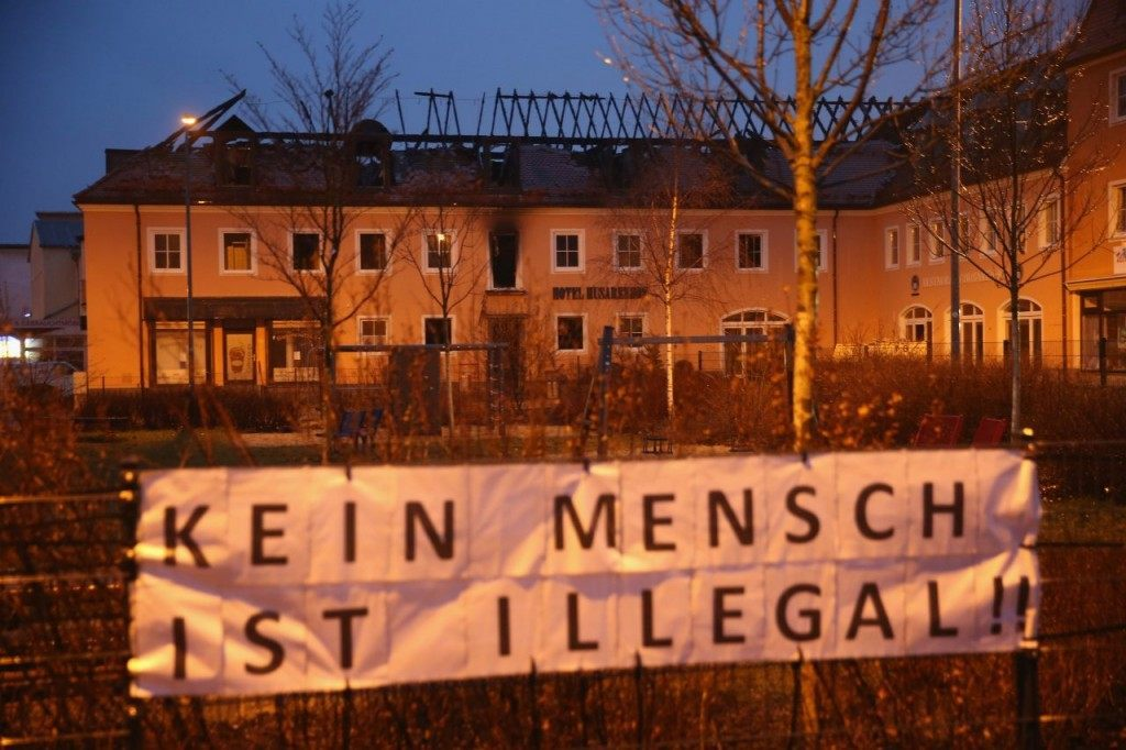 A pro-migrant sign is hung outside the building the night after the fire (Sean Gallup/Getty Images)