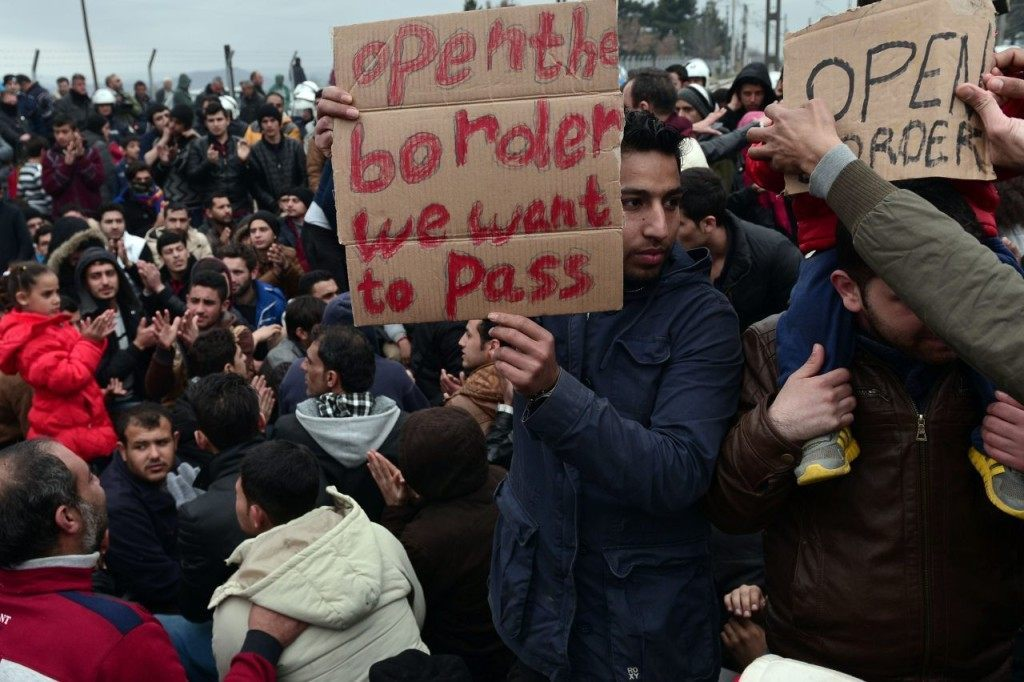 Syrian and Iraqi refugees trapped at the Greek-Macedonian border protest demanding the opening of the borders on February 28, 2016. More than 5,000 people were trapped at the Idomeni camp after four Balkan countries announced a daily cap on migrant arrivals. Slovenia and Croatia, both EU members, and Serbia and Macedonia said they would restrict the number of daily arrivals to 580 per day. / AFP / LOUISA GOULIAMAKI (Photo credit should read LOUISA GOULIAMAKI/AFP/Getty Images)