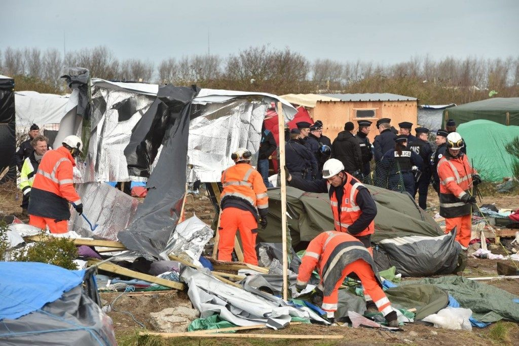 "Agents dismantle shelters on February 29, 2016 in the ""jungle"" migrants and refugees camp in Calais, northern France. A French court on February 25 gave the green light to plans to evacuate hundreds of migrants from the southern half of the sprawling camp in the port town, with many of the migrants wanting to stay near the entrance to the Channel Tunnel, the gateway to their ultimate goal of Britain. AFP PHOTO / PHILIPPE HUGUEN / AFP / PHILIPPE HUGUEN (Photo credit should read PHILIPPE HUGUEN/AFP/Getty Images)"