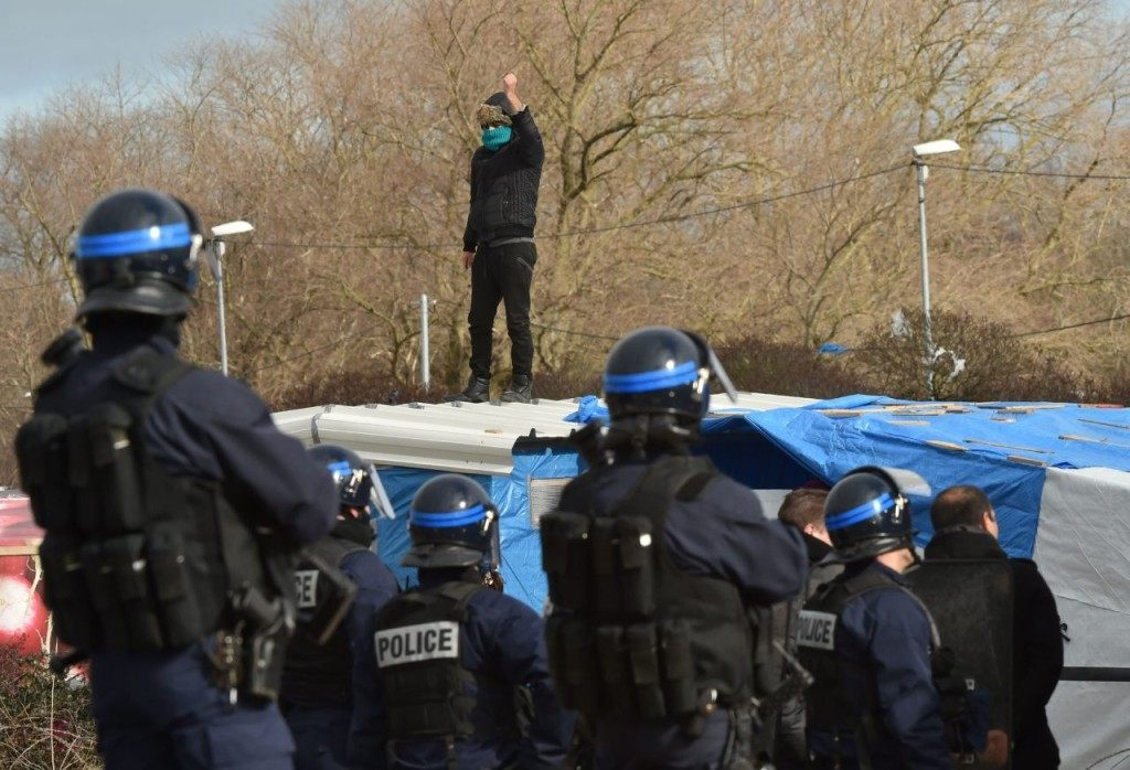 "A man on a shelter's roof refusing to leave gestures in front of anti-riot policemen as agents dismantle shelters on February 29, 2016 in the ""jungle"" migrants and refugees camp in Calais, northern France. A French court on February 25 gave the green light to plans to evacuate hundreds of migrants from the southern half of the sprawling camp in the port town, with many wanting to stay near the entrance to the Channel Tunnel, the gateway to their ultimate goal of Britain. AFP PHOTO / PHILIPPE HUGUEN / AFP / PHILIPPE HUGUEN (Photo credit should read PHILIPPE HUGUEN/AFP/Getty Images)"
