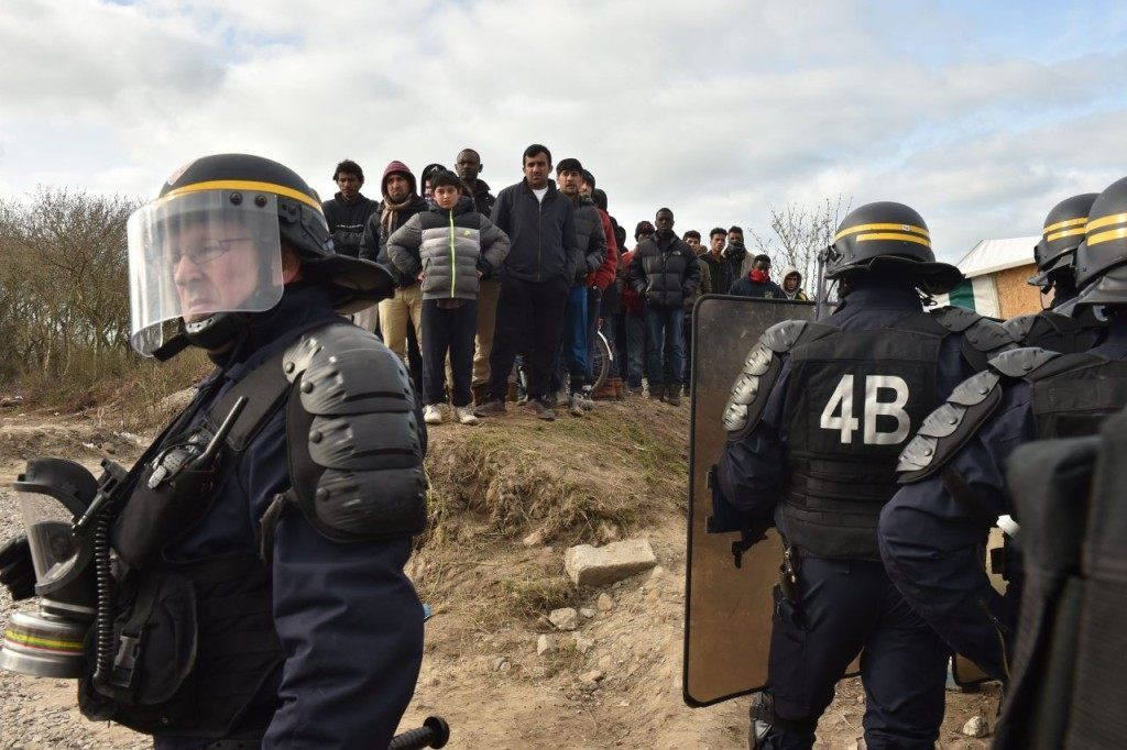 "Anti-riot policemen face migrants on February 29, 2016, during the dismantling of half of the ""Jungle"" migrant camp in the French northern port city of Calais. Two bulldozers and around 20 workers began destroying makeshift shacks, with 30 police cars and two anti-riot vans stationed nearby. AFP PHOTO / PHILIPPE HUGUEN / AFP / PHILIPPE HUGUEN (Photo credit should read PHILIPPE HUGUEN/AFP/Getty Images)"