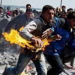 A man runs after he tried to put himself on fire during a protest at a makeshift camp at the Greek-Macedonian border near the village of Idomeni on March 22, 2016. Greece will not be able to start sending refugees back to Turkey from March 20, 2016, the government said, as the country struggles to implement a key deal aimed at easing Europe's migrant crisis. The numbers are daunting: officials said as of Saturday there were 47,500 migrants in Greece, including 8,200 on the islands and 10,500 massed at the Idomeni camp on the Macedonian border. / AFP / ANDREJ ISAKOVIC (Photo credit should read ANDREJ ISAKOVIC/AFP/Getty Images)