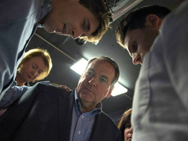 Presidential Candidate Mike Huckabee stands in a prayer circle with his supporters after speaking at Inspired Grounds coffee shop in West Des Moines, Iowa, January 31, 2016, ahead of the Iowa Caucus. / AFP / Jim WATSON (Photo credit should read
