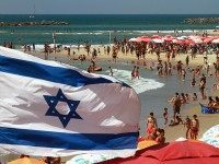 An Israeli flag flutters above umbrellas on the beach in the Mediterranean city of Tel Aviv on August 11, 2015. Decision to dedicate a day of beach parties in the French capital to Israel's most famous beach city sparks condemnation from pro-Palestinian group saying it sends 'very bad message' of …