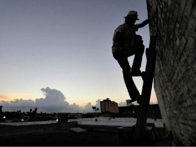 Man Climbing Border Wall AP PhotoEric Gay