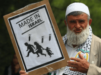 A pro-Palestinian demonstrator holds up an anti-Israel poster during a demonstration at the residence entrance of Israel's ambassador to Turkey Gabby Levy, in Ankara, on June 2, 2010 after the May 31 bloodshed on the Gaza-bound aid flotilla.