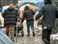 Migrants walk between tents on February 18, 2016 in the refugee and migrant camp in Grande-Synthe, France