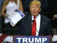 Republican presidential candidate Donald Trump tosses a paper into the crowd as he speaks during a campaign rally at the University of South Florida Sun Dome on February 12, 2016 in Tampa, Florida.