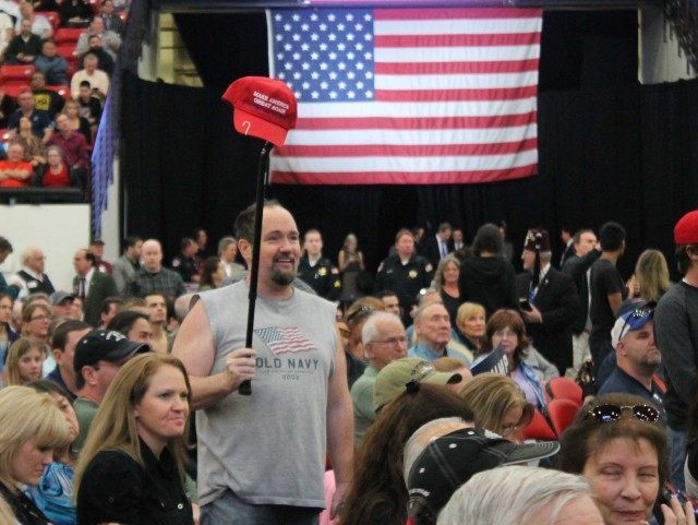 Trump supporter hoists hat (Joel Pollak / Breitbart News)