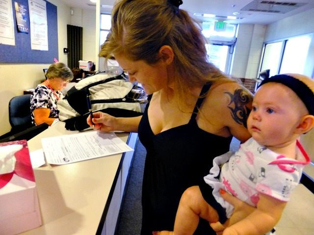 In this July 16, 2012, photo, Laura Fritz, 27, left, with her daughter Adalade Goudeseune fills out a form at the Jefferson Action Center, an assistance center in the Denver suburb of Lakewood. Both Fritz grew up in the Denver suburbs a solidly middle class family, but she and her …