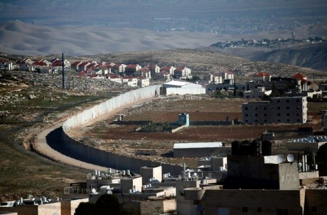 A section of Israel's separation barrier in east Jerusalem divides the Palestinian Shuafat refugee camp (right) from the Jewish settlement Pisgat Zeev