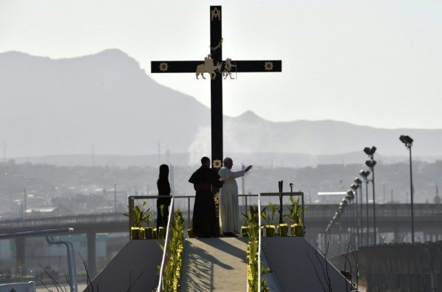 Pope Francis waves next to the US border before celebrating mass at the Ciudad Juarez fairgrounds in Mexico on February 17, 2016