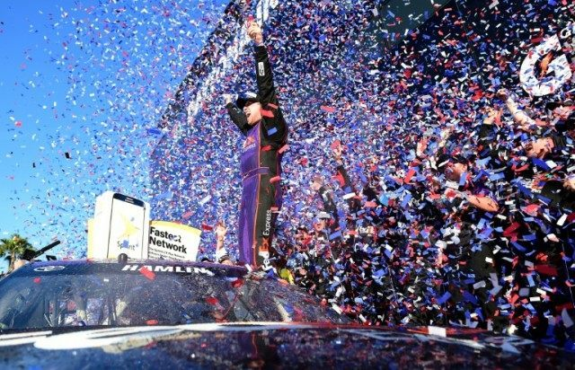 Denny Hamlin, driver of the #11 FedEx Express Toyota, celebrates in Victory Lane after winning the Daytona 500 on February 21, 2016 in Daytona Beach, Florida