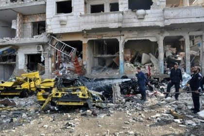 Syrian firefighters spray water on burning car at the site of a double car bomb attack in the Al-Zahraa neighborhood of the central Syrian city of Homs on February 21, 2016