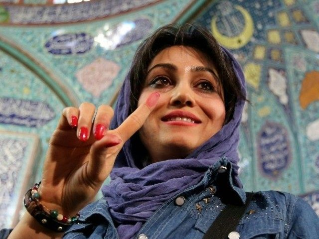 An Iranian woman displays her ink-stained finger after casting her ballot for both parliamentary elections and the Assembly of Experts at a polling station in Tehran, on February 26, 2016