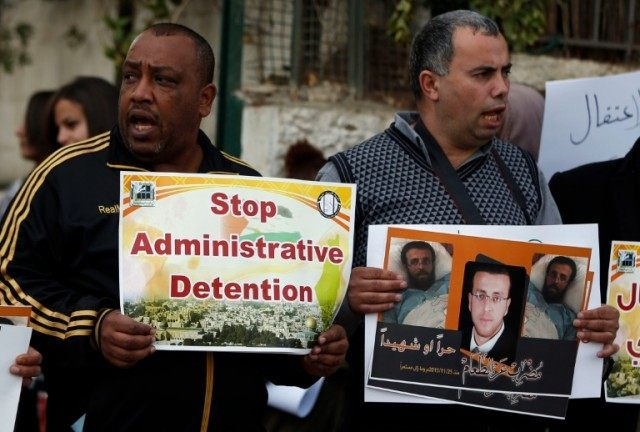 Palestinians call for the release of Mohammed al-Qiq, a Palestinian prisoner on hunger strike, outside the Red Cross building in Jerusalem on February 18, 2016