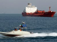 An Iranian Revolutionary Guard speedboat cruises past an oil tanker off the port of Bandar Abbas, Iran, on July 2, 2012, in recent years, Iranian oil exports have fallen from more than 2.2 million barrels per day to about one million